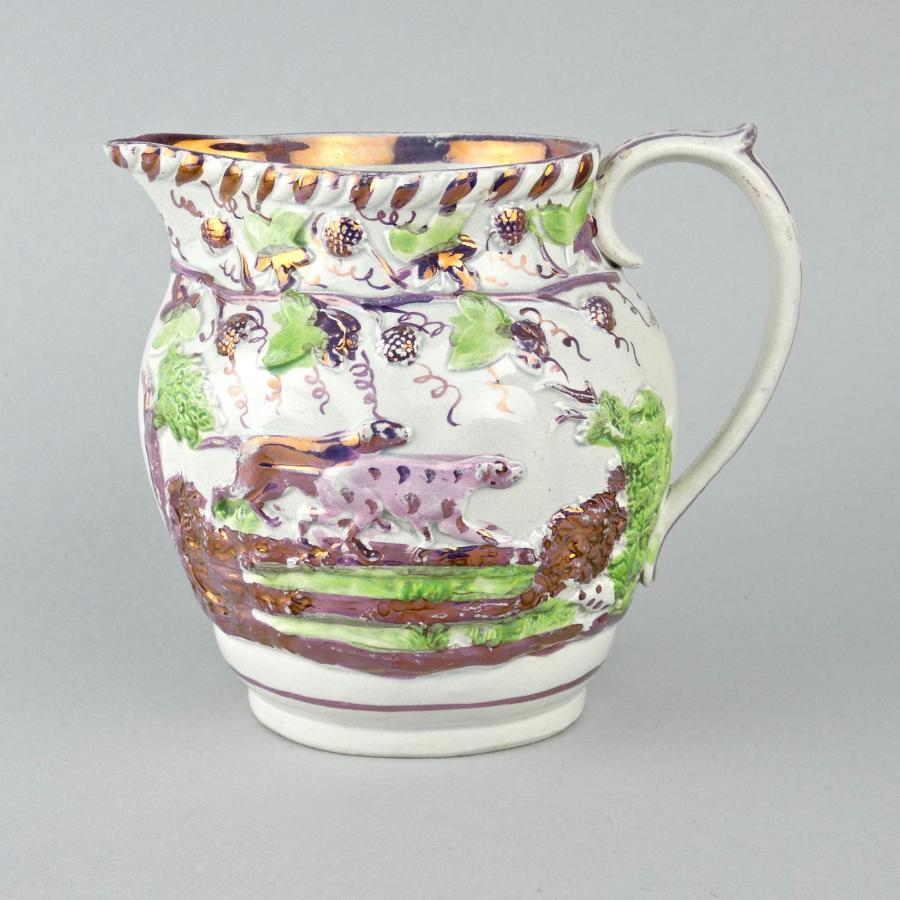 Pink lustre jug moulded with dogs.