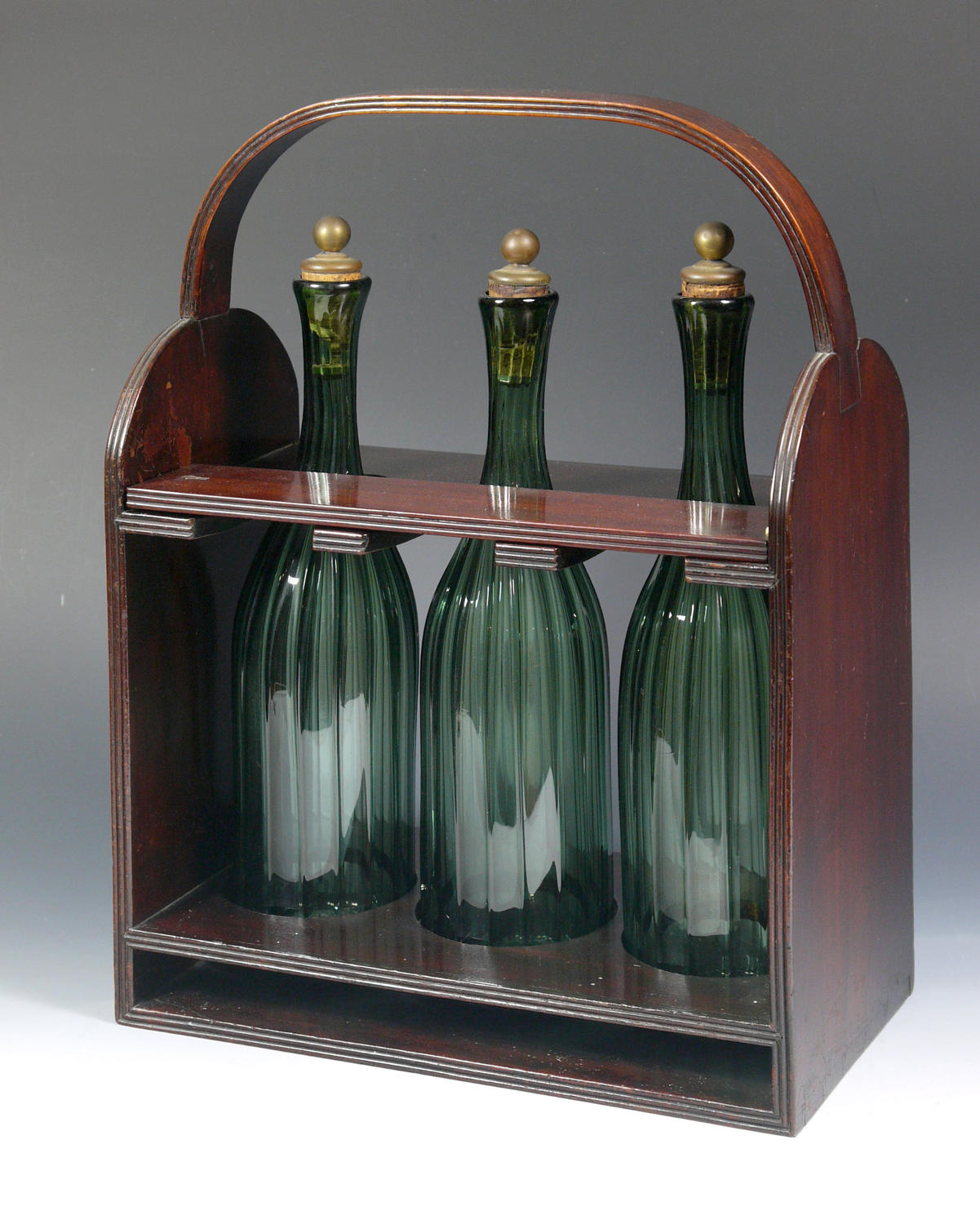 An unusual mahogany tantalus with green bottles