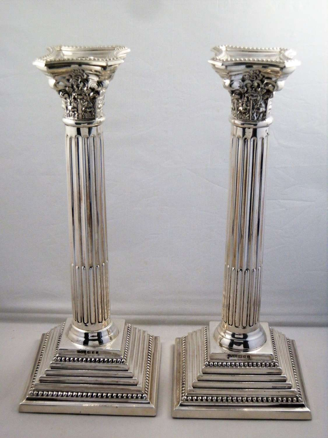 Pair of silver corinthian candle sticks, London 1960