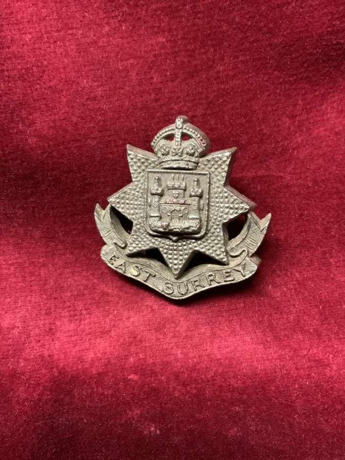 The East Surrey Regiment Silver Coloured Plastic Cap Badge