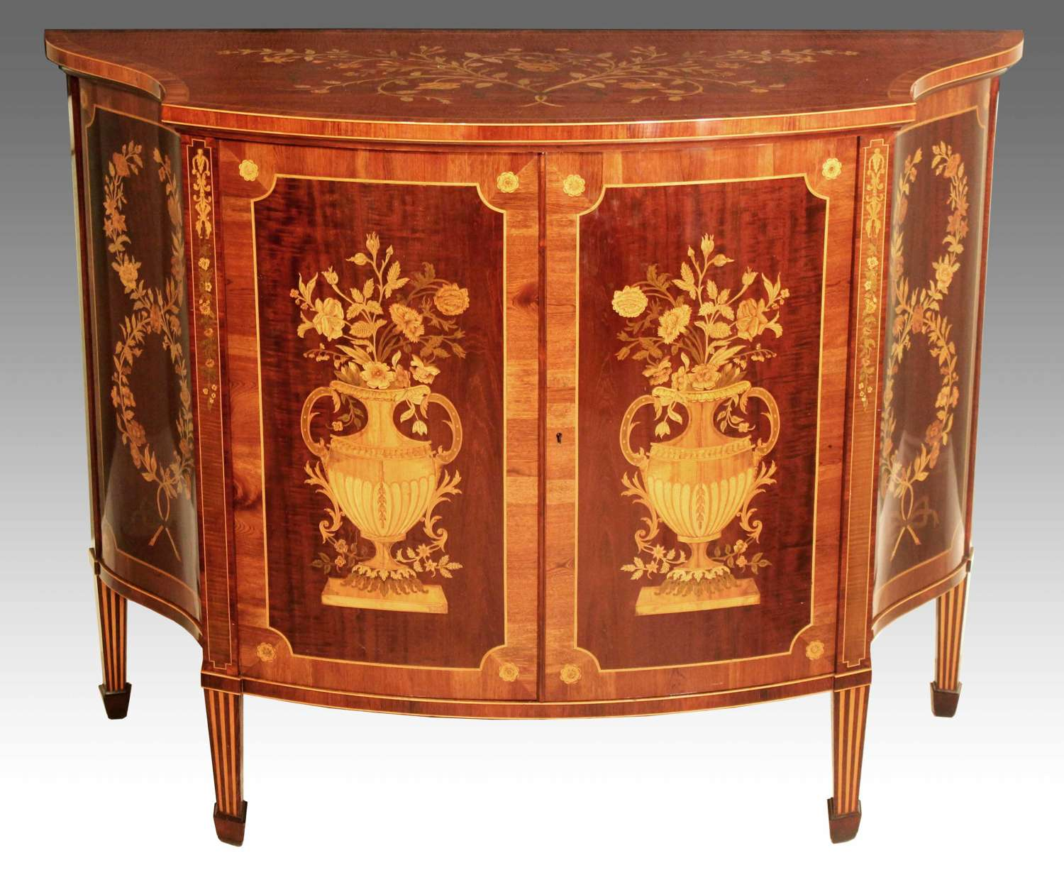 A Superb Late Victorian Mahogany Inlaid Serpentine Commode